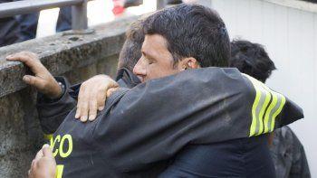 Fotografía facilitada por el Palacio Chigi del gobierno italiano que muestra al primer ministro Matteo Renzi (d) abranzando a los voluntarios que trabajan en las labores de rescate tras el terremoto en la localidad de Amatrice, en el centro deItalia