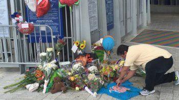 Un hombre escribe sobre una camiseta en el lugar donde los vecinos de La Pequeña Habana decidieron rendir homenaje al fallecido lanzador José Fernández, en el Marlins Park.