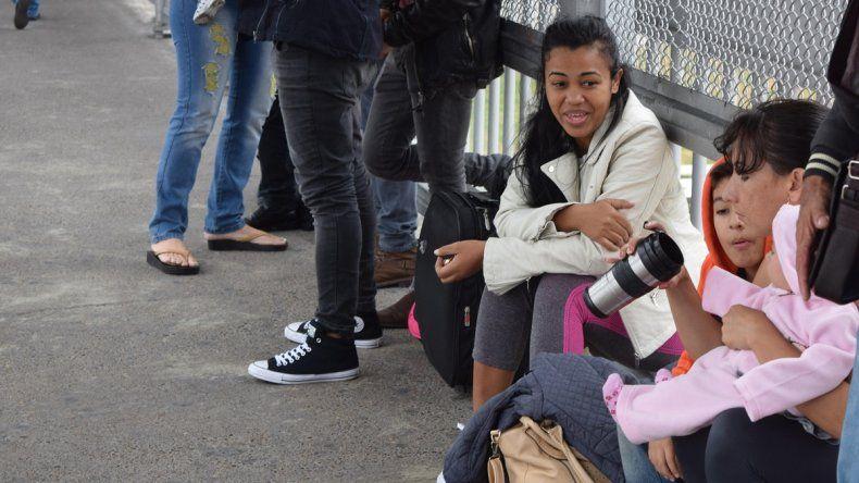 La cubana Irina Vicardo (d), madre de dos niños de 8 años y 1 año, espera sentada mientras cubanos se manifiestan de forma pacífica formando una fila en la puerta de entrada a Estados Unidos en Laredo, Texas