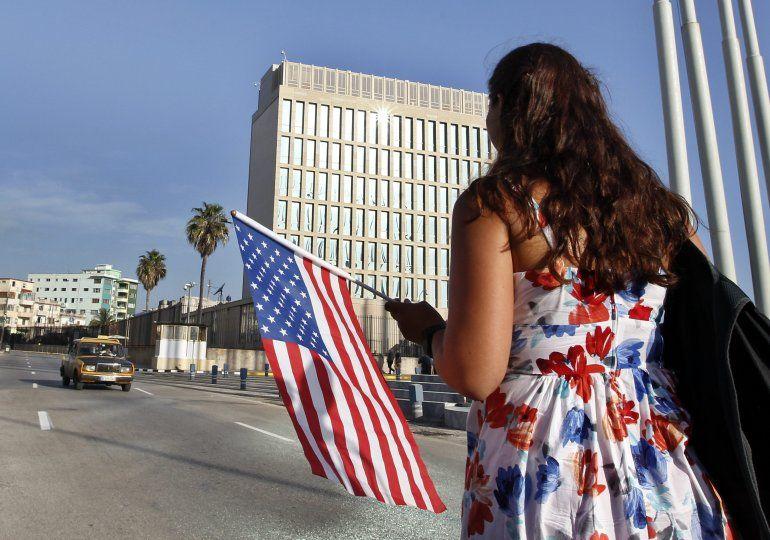 Una mujer camina con una bandera estadounidense frente a la embajada de ese país en La Habana.