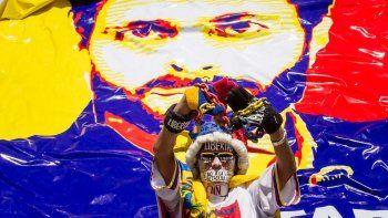 Un manifestante con su rostro pintado, su boca cubierta y sus manos atadas a una cadena, participa junto a cientos de personas en una marcha para exigir la liberación de Leopoldo López, este sábado 18 de febrero de 2017, en Caracas, Venezuela.