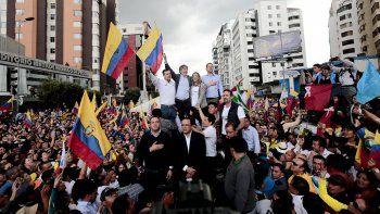 El candidato presidencial ecuatoriano de oposición, Guillermo Lasso (c-i), saluda a sus seguidores en Quito