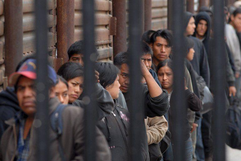 Indocumentados forman una fila mientras esperan ser deportados en San Diego, California (EEUU), en el cruce peatonal fronterizo que conduce a Tijuana, México.