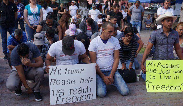 """Ciudadanos cubanos varados en México se manifiestan el sábado 8 de abril de 2017, frente al puente fronterizo de Nuevo Laredo,  para pedir al pesidente Trump que reconsidere la decisión de Estados Unidos de poner fin a su política de """"pies secos/pies mojados""""."""