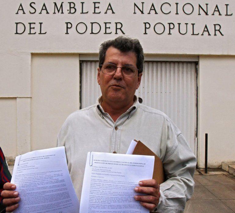Oswaldo Payá habla con la prensa frente a la sede del cuerpo legislativo cubano, el día que entregó las firmas para solicitar un plebiscito.