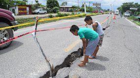 Unos niños observan una grieta que se abrió en la parte mexicana del camino en la línea divisoria conGuatemala, donde se han producido varias réplicas de un sismo de 6,7 en la escala de Richter, que sacudió a ese país.