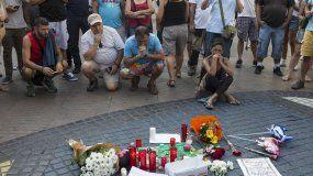 Varias personas se paran frente al mosaico de Miró en las Ramblas deBarcelonadespués del atentado ocurrido ayer por la tarde en un atropello masivo en el que una furgoneta arrolló a los peatones.