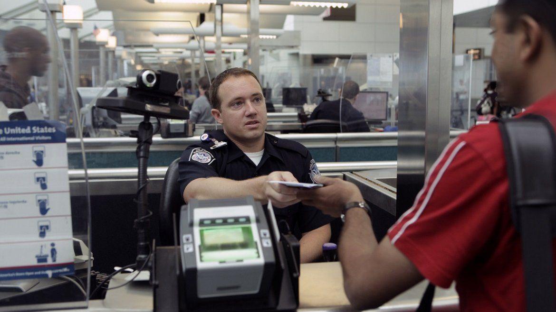 Un oficial del Servicio de Inmigración de los EEUU chequea los documentos de un hombre en un punto de entrada a los EEUU.