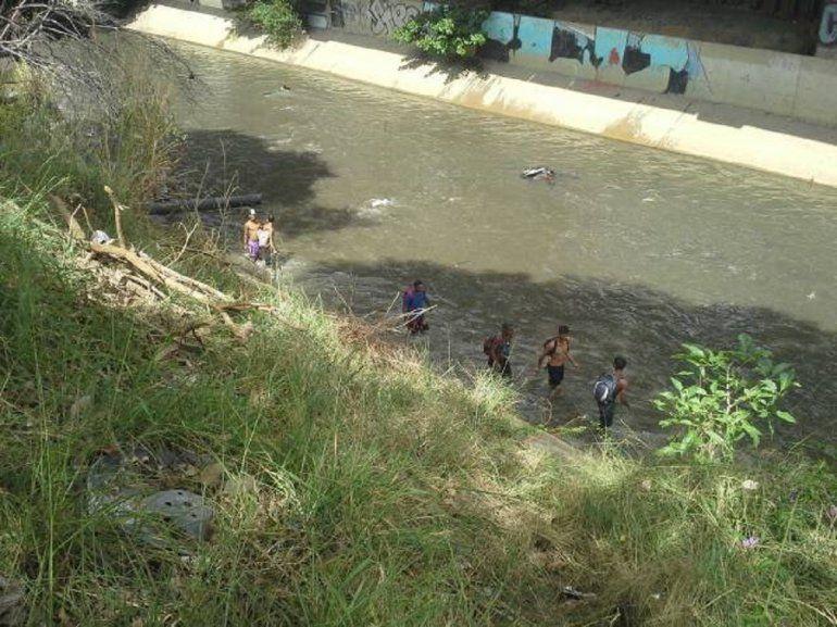 Jóvenes caminan por las riberas del Guaire, un río de cloaca, buscando oro.