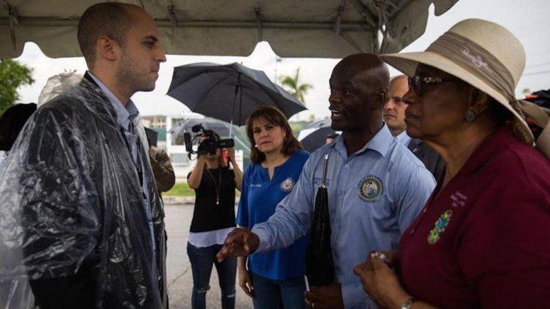 La representante estatal Kionne McGhee y la comisionada del condado de Miami-Dade, Barbara Jordan, hablan con un funcionario de la instalación de Homestead que alberga a niños inmigrantes separados de sus padres.