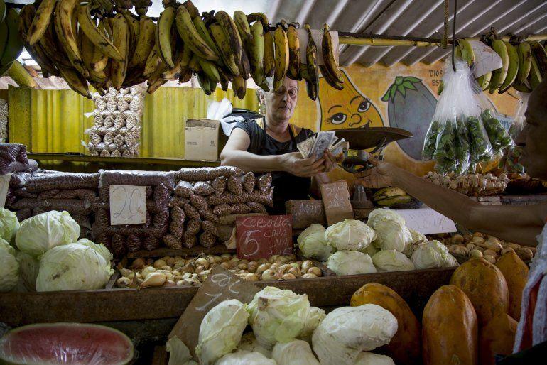 Una mujer cuenta dinero luego de vender unas verduras a un cliente en su puesto en La Habana, Cuba, el miércoles 30 de julio de 2019.