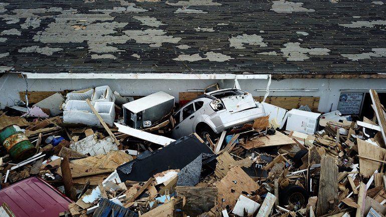 Un cúmulo de escombros envuelven dos vehículos alrededor de una vivienda destruida por el huracán Dorian en Marsh Harbour en Great Abaco Island, Bahamas el jueves 5 de septiembre de 2019.