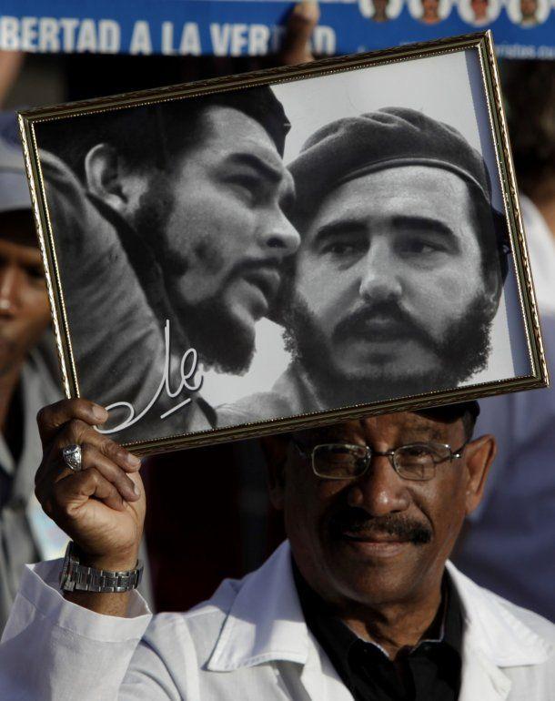 Fotografía del 1ro de mayo de 2009 de un hombre que sostiene una foto del Che Guevara y Fidel Castro en La Habana, Cuba.