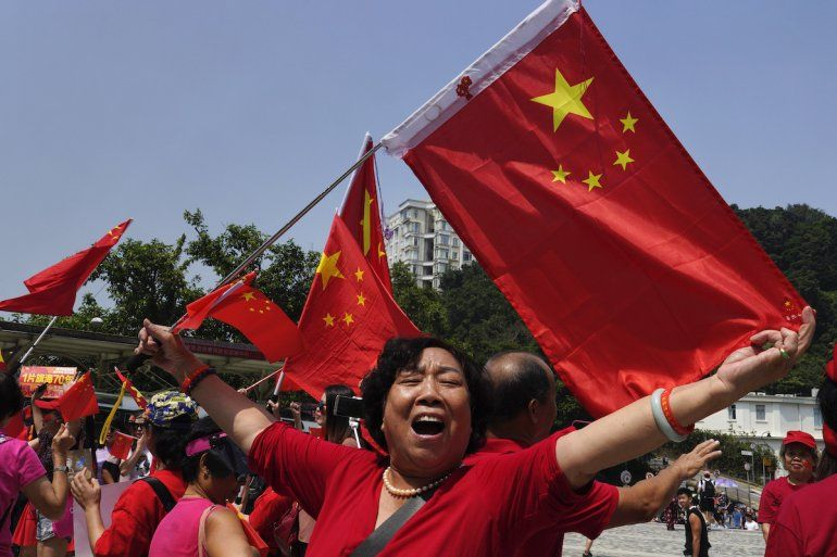 Una partidaria de China ondea una bandera china en el Peak en Hong Kong, el domingo 29 de septiembre de 2019.