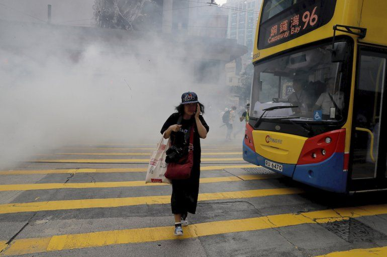 Una mujer camina junto a una nube de gas lacrimógeno, durante una protesta en Hong Kong, el domingo 29 de septiembre de 2019.