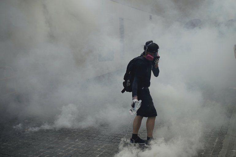 Un manifestante contrario al gobierno camina entre el gas lacrimógeno, en medio de choques con la policía en la zona de Wong Tai Sin en Hong Kong, el martes 1 de octubre de 2019.