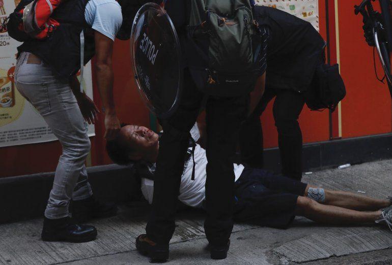 Un manifestante herido es asistido por otros durante un choque con la policía en Hong Kong, martes 1 de octubre de 2019.