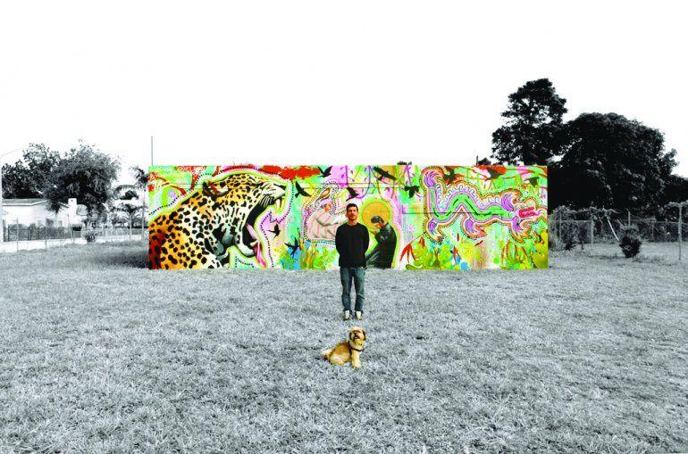 El artista Luis Valle muestra uno de sus murales.