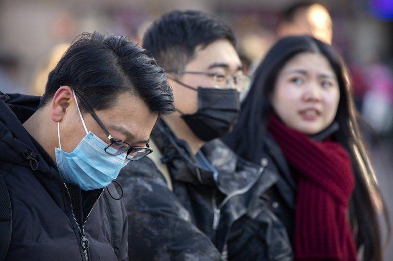 Personas utilizan cubrebocas afuera de la estación de trenes en Beijing el lunes 20 de enero de 2020.