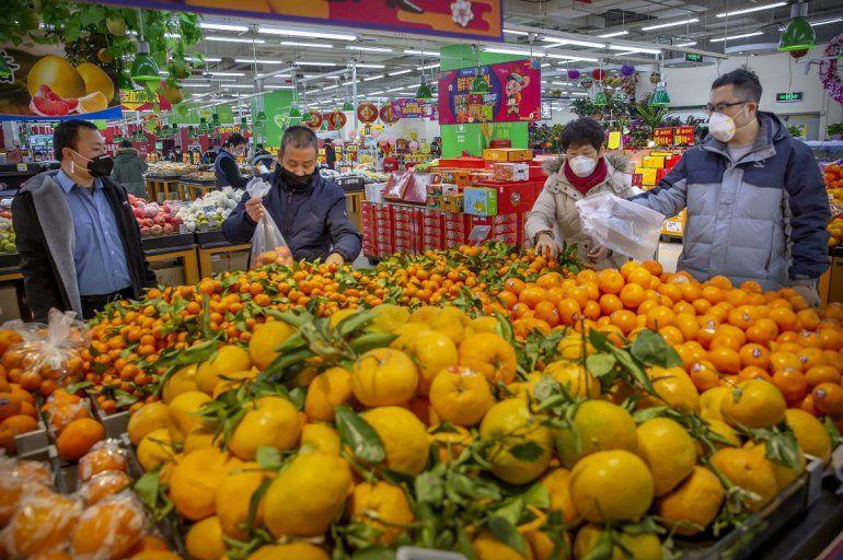 Varias personas compran cítricos en un supermercado de Beijing, protegidos por una mascarilla facial, en Beijing, China, el 28 de enero de 2020.