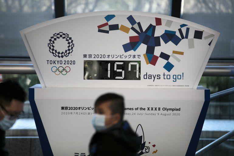En esta fotografía del martes 18 de febrero de 2020, unas personas que portan mascarillas caminan frente a un reloj de cuenta regresiva para los Juegos Olímpicos en Tokio.