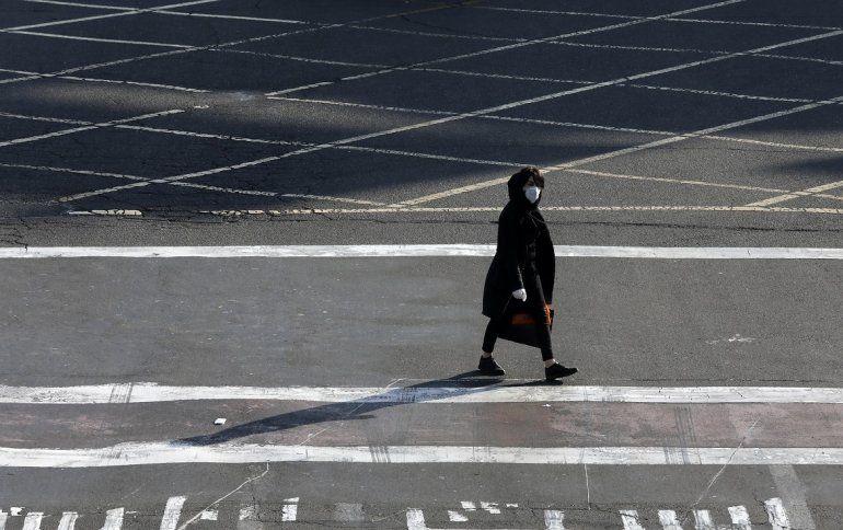Una mujer con mascarilla y guantes pasa por un cruce en el norte de Teherán, Irán, el 4 de marzo de 2020.