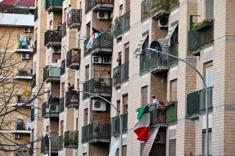 Varios residentes de un edificio muestran la bandera italiana este domingo durante la cuarentena.