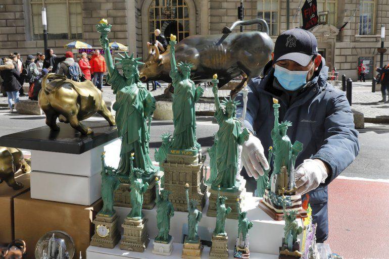 Un vendedor porta guantes y una mascarilla mientras trabaja en la ciudad de Nueva York, el domingo 15 de marzo de 2020. El temor al coronavirus se expande en toda la nación.