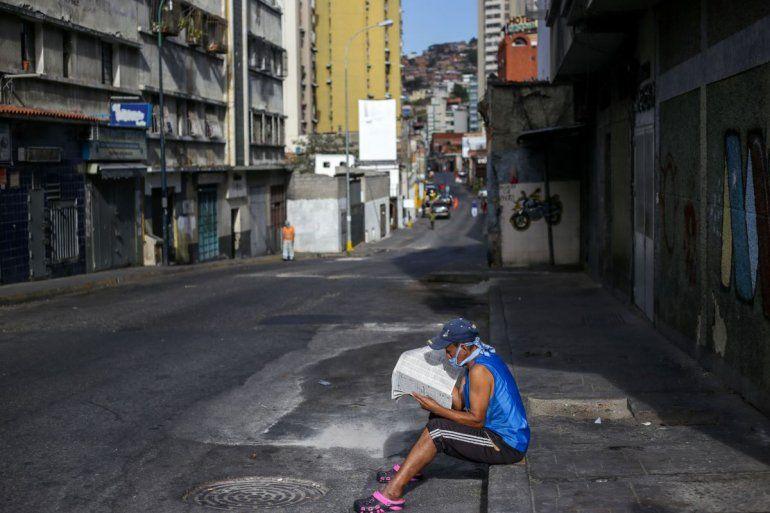 Un hombre usa una máscarilla como medida preventiva contra la pandemia mundial de coronavirus COVID-19 mientras lee el periódico en una calle vacía en Caracas, el 21 de marzo de 2020.