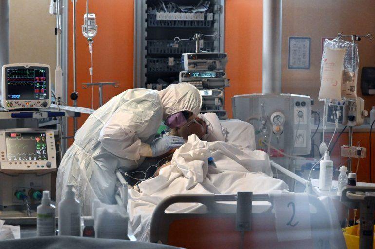 Un trabajador médico con equipo de protección atiende a un paciente el 24 de marzo de 2020 en la nueva unidad de cuidados intensivos para casos de coronavirus COVID-19, en el hospital Casal Palocco en Roma, Italia.