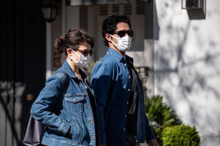 Dos personas caminan en París con mascarillas de protección.