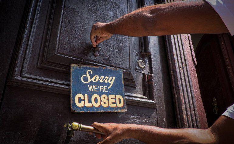Una persona coloca el cartel de cerrado a las puertas de un café, en La Habana, Cuba.