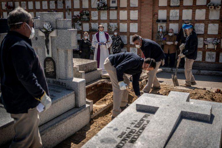 Un sacerdote y varios dolientes rezan mientras una víctima del COVID-19 es enterrada en el cementerio de la Almudena, en Madrid, España, el sábado 28 de marzo de 2020.