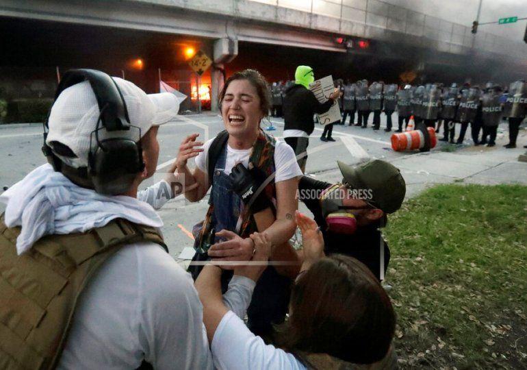Los manifestantes ayudan a una mujer que recibió un disparo en la garganta con una bala de goma durante las protestas que se tornaron violentas en la ciudad de Miami, el sábado 30 de mayo de 2020.