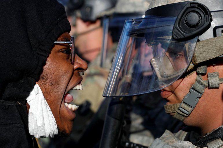 Un manifestante grita en el rostro a un efectivo de la Guardia Nacional durante una manifestación en la calle East Lake, en St. Paul, Minnesota.