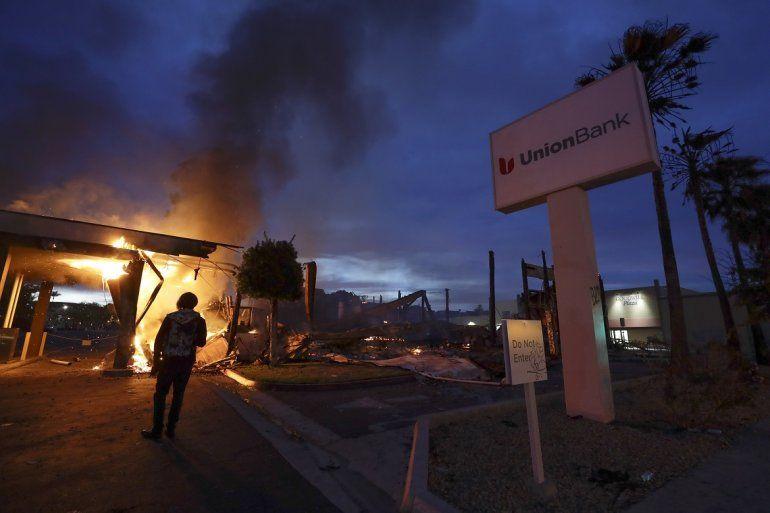 Una persona en la Mesa, California, observa mientras se incendia un banco el domingo 31 de mayo de 2020 durante los disturbios por la muerte hace unos días de George Floyd en Minneapolis.