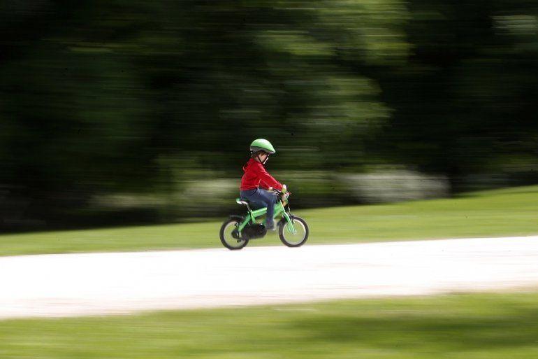 Un niño anda en bici en un parque recién abierto después de varias semanas cerrado debido a la cuarentena por el coronavirus, el 4 de mayo de 2020 en Milán, Italia.