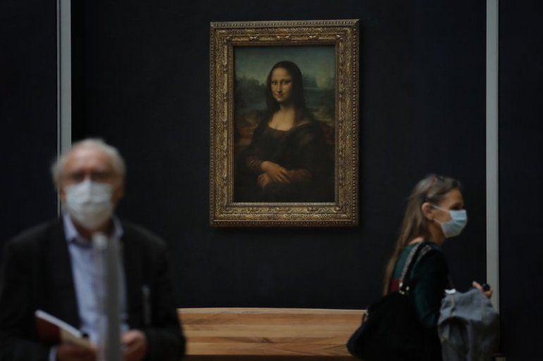 """Periodistas pasan frente a la Mona Lisa de Leonardo da Vinci durante una visita al museo del Louvre previa a su reapertura el 6 de julio en París, el martes 23 de junio de 2020. Después de cuatro meses sin recibir visitantes por el brote de coronavirus la """"Mona Lisa"""" se prepara para atraer nuevamente a visitantes cuando el Louvre reabra en julio."""