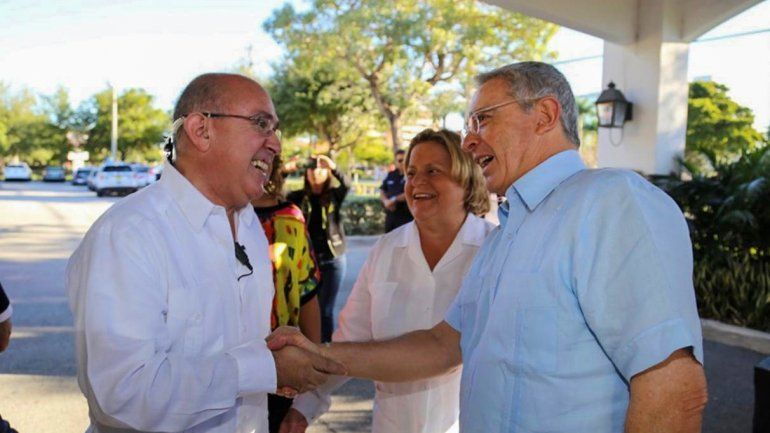 El expresidente Álvaro Uribe (der.) estrecha su mano al activista colombiano Fabio Andrade. Observa la excongresista federal Ileana Ros-Lehtinen.