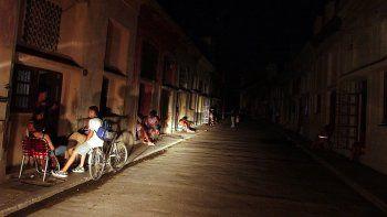 Varias personas conversan iluminadas por la luz de un automóvil en una calle del populoso barrio El Cerro, en La Habana, Cuba.