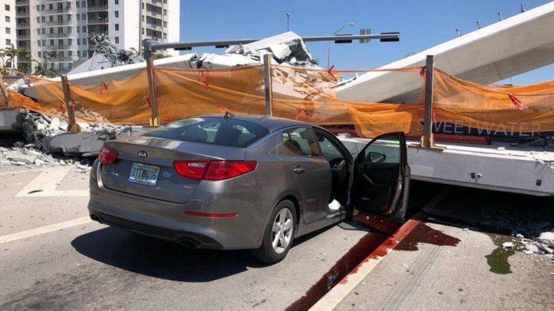 Vista de uno de los autos que quedó atrapado bajo la estructura del puente peatonal que colapsó frente a la Universidad Internacional de la Florida, en Miami.