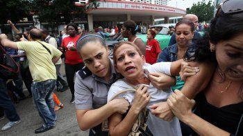 Una de las integrantes de las Dama de Blanco es reprimida por agentes de la policía política en La Habana, Cuba.