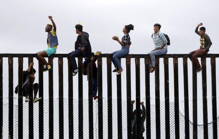 Algunos de los manifestantes treparon hasta la parte más alta de los postes de la valla fronteriza.