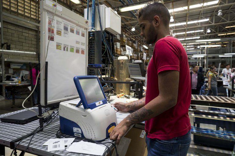 Un trabajador del Consejo Nacional Electoral de Venezuela (CNE) revisa una de las máquinas que se utilizan en las elecciones presidenciales.