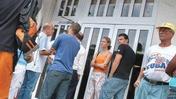 Varias personas hacen cola en las puertas de un banco de la capital cubana.