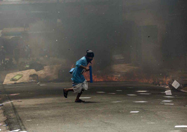 Un joven corre frente a una barricada durante un enfrentamiento con la policía nacional en la ciudad de Masaya (Nicaragua).