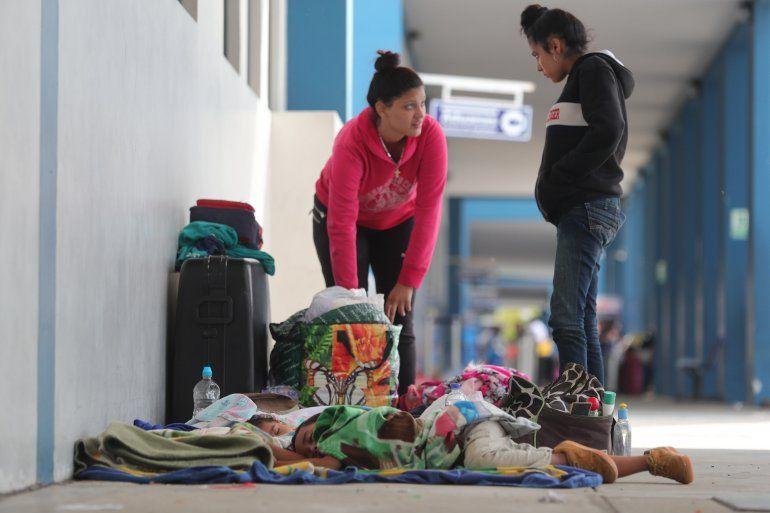 Dos niños venezolanos duermen en el suelo sobre cartones mientras familiares cuidan sus pertenencias esperando continuar su camino hacia Perú.