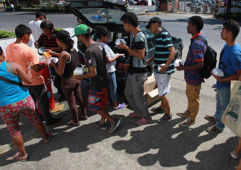 Un grupo de venezolanos hacen fila para recibir un poco de comida que entregan personas voluntarias en Cali, Colombia.