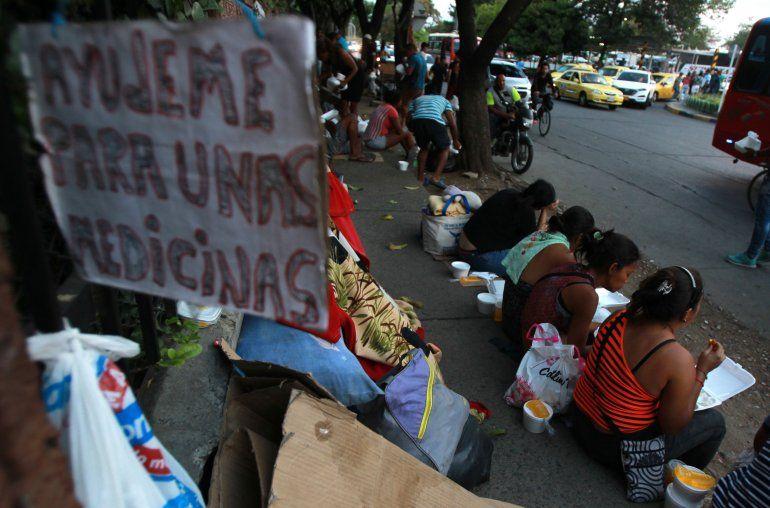 Venezolanos comen en las afueras de la terminal de transportes en Cali (Colombia).