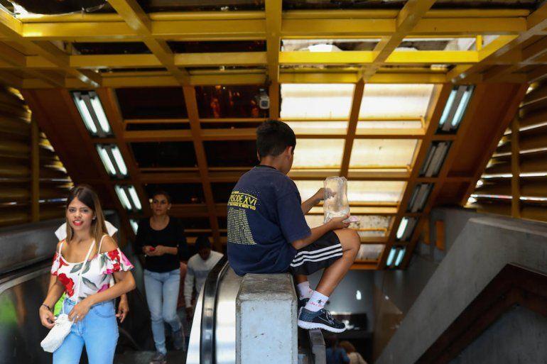 Un niño pide dinero a las puertas del Metro de Caracas.